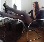 Sophia is sitting at her computer desk wearing a black lace dress, black high heels and smoky...