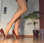Knie vor meinen roten High Heels