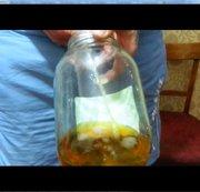 Ein Mann pisses in einem Glasdreiliter-Glas.