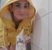 Duschen in neuen Gummistiefeln und Regenmantel
